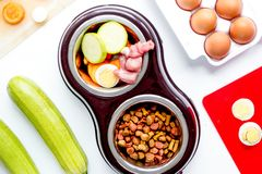 Petfood set with vegetables and eggs on kitchen table background stock image