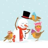 Petirrojos y muñeco de nieve Fotos de archivo libres de regalías