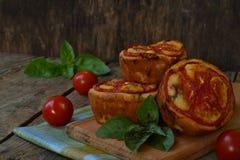 Petisco salgado Queques caseiros com queijo, tomates e manjericão no fundo de madeira Pastelaria saboroso fotos de stock royalty free