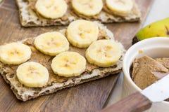 Petisco saudável do vegetariano com o pão estaladiço escandinavo do centeio, manteiga de amendoim caseiro e fatias de bananas Imagens de Stock Royalty Free