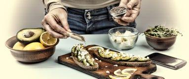 Petisco saudável A mulher está preparando sanduíches com abacate e rúcula em casa foto de stock