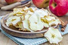 Petisco saudável Microplaquetas caseiros da maçã no fundo de madeira Imagem de Stock