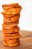 Petiscos com a pimenta e os oréganos empilhados na placa de madeira Foto de Stock