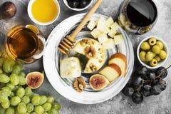 Petiscos com vinho - vários tipos de queijos, figos, porcas, mel, Foto de Stock
