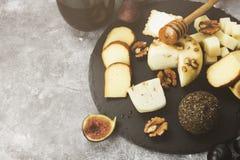 Petiscos com vinho - vários tipos de queijos, figos, porcas, mel, Fotografia de Stock