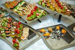 Petiscos de abastecimento do serviço do grupo da tabela vários em uma tabela no banquete Grupo de petiscos frios, canape, bebidas fotos de stock royalty free