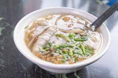 Petiscos famosos distintivos do ` s de Taiwan: pesque a sopa do potage da almôndega em uma bacia branca na tabela de pedra, gulos fotos de stock