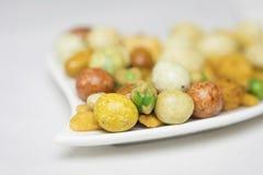 Petiscos misturados, porcas e feijões verdes salgados em uma placa branca Fotografia de Stock Royalty Free