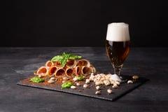 Petiscos para a cerveja Um vidro completo da cerveja e da espuma, pistaches e prosciutto temperados com pimenta e manjericão em u fotografia de stock