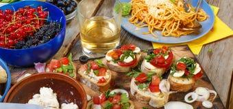 Petiscos variados na mesa de jantar, no vinho, na massa e nos bruschettes com abacate e close up dos tomates de cereja Imagem de Stock