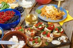 Petiscos variados na mesa de jantar, no vinho, na massa e nos bruschettes com abacate e close up dos tomates de cereja Imagens de Stock