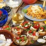 Petiscos variados na mesa de jantar, no vinho, na massa e nos bruschettes com abacate e close up dos tomates de cereja Fotos de Stock