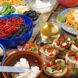 Petiscos variados na mesa de jantar, no vinho, na massa e nos bruschettes com abacate e close up dos tomates de cereja Imagem de Stock Royalty Free