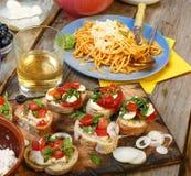 Petiscos variados na mesa de jantar, no vinho, na massa e nos bruschettes com abacate e close up dos tomates de cereja Fotografia de Stock Royalty Free