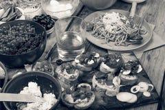 Petiscos variados na mesa de jantar, no vinho, na massa e nos bruschettes com abacate e close up dos tomates de cereja Fotografia de Stock