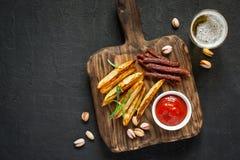 Petiscos variados para a cerveja Porcas fritadas dos pepperoni das batatas e um vidro da cerveja Fotografia de Stock Royalty Free