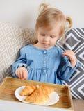 Petit âge de bébé de 1,11 ans mangeant des croissants Image libre de droits