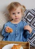 Petit âge de bébé de 1,11 ans mangeant des croissants Photos stock