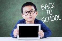 Petit écolier de nouveau au comprimé d'école et de prises Image stock
