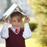 Petit écolier de portrait sur le fond de nature Enfant avec des livres Image libre de droits