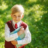 Petit écolier de portrait sur le fond de nature Enfant avec des livres Photo stock