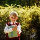 Petit écolier de portrait sur le fond de nature Enfant avec des livres Photos stock