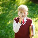 Petit écolier de portrait sur le fond de nature Enfant avec des livres Photographie stock