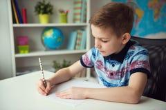 Petit écolier futé faisant des devoirs au bureau dans la chambre Photo stock