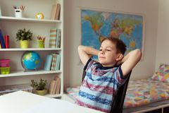 Petit écolier futé faisant des devoirs au bureau dans la chambre Photographie stock libre de droits