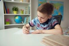 Petit écolier futé faisant des devoirs au bureau dans la chambre Photos stock