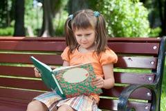 Petit élève du cours préparatoire mignon de fille avec le livre sur le banc Photographie stock