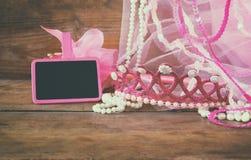 Petit équipement de partie de filles : la couronne et la baguette magique fleurit à côté du petit tableau vide sur la table en bo images libres de droits