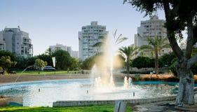 Petit étang avec la fontaine en parc de ville au coucher du soleil Images libres de droits
