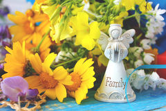 Petit ange blanc de famille sur une table bleue en bois avec un bouque Photographie stock libre de droits