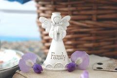 Petit ange blanc de famille sur une table bleue en bois avec un bouque Image libre de droits