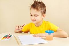 Petit artiste dans la chemise jaune allant peindre des couleurs Photographie stock