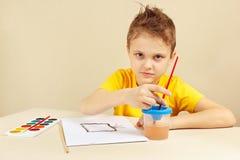 Petit artiste dans la peinture jaune de chemise avec des aquarelles images stock