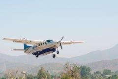 Petit avion bleu et blanc décollant avec des montagnes à l'arrière-plan Photo stock