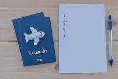 Petit avion de jouet sur un passeport bleu et un carnet blanc Images libres de droits