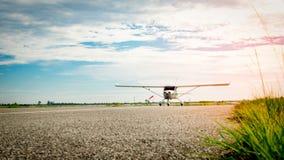 Petit avion venant sur une piste de roulement pendant le matin Durée lumineuse Forte croissance et concept à haut risque d'affair images libres de droits