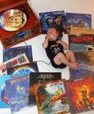 Petit bébé écoutant la musique de métaux lourds, un genre de la musique rock créé pendant les années 70 Photos stock