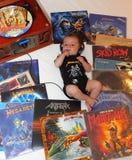 Petit bébé écoutant la musique de métaux lourds, un genre de la musique rock créé pendant les années 70 Images stock