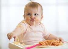 Petit bébé adorable un an mangeant des pâtes d'intérieur Enfant drôle d'enfant en bas âge avec des spaghetti Enfant mignon et nou photo libre de droits