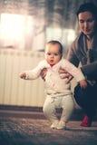 Petit bébé apprenant à marcher avec l'aide de mère à la maison image stock