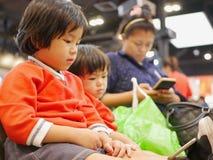 Petit bébé asiatique, ainsi que sa plus jeune soeur, observant un smartphone, mêmes que sa maman, reposant et attendant une file  image stock