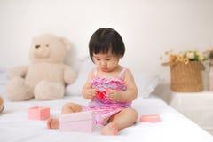 Petit bébé asiatique mignon s'asseyant sur jouer de lit Photos stock