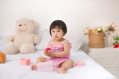 Petit bébé asiatique mignon s'asseyant sur jouer de lit Photo libre de droits