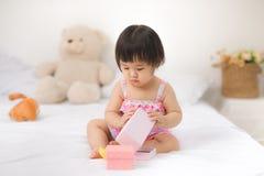 Petit bébé asiatique mignon s'asseyant sur jouer de lit Image libre de droits