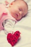 Petit bébé avec le jouet de forme de coeur Image libre de droits