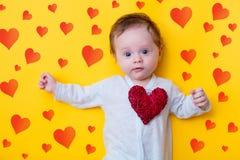 Petit bébé avec le jouet rouge de forme de coeur Photographie stock
